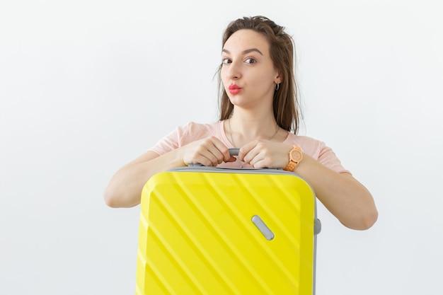 Концепция поездки, путешествий и праздников - женщина с желтым чемоданом над белой стеной Premium Фотографии