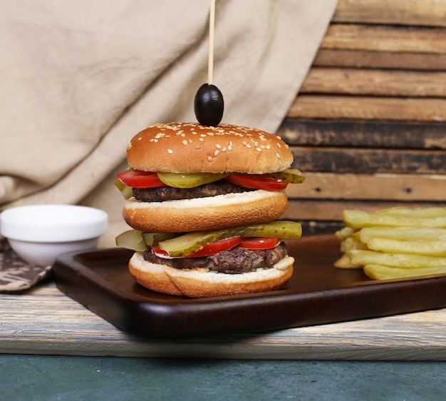 Triple burger with meat and vegetables. Free Photo