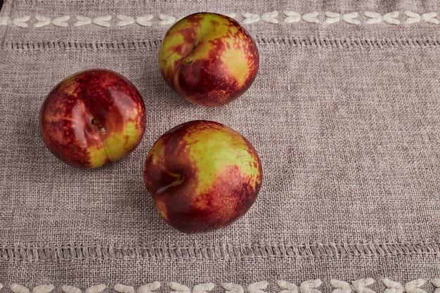 台所のテーブルで隔離の三重の赤いリンゴ。 無料写真