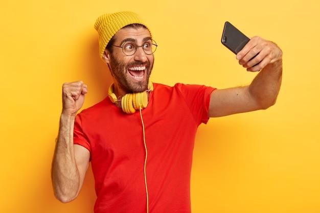 L'uomo felice trionfante celebra il successo, fa foto di se stesso, scatta selfie, gira video, indossa cappello, maglietta e occhiali isolati su sfondo giallo. persone Foto Gratuite