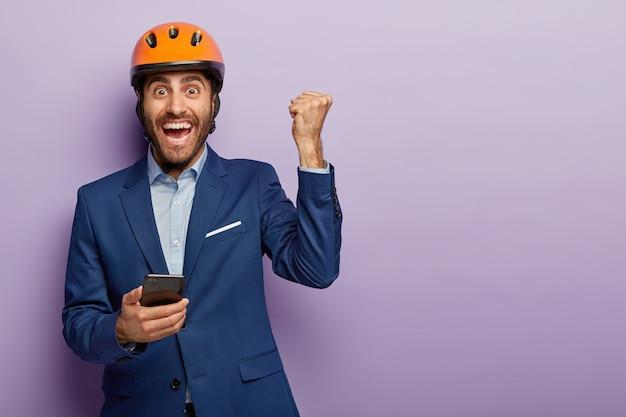 행복한 엔지니어가 휴대 전화를 들고 주먹을 움켜 쥐고 전화를 사용하며 건설 현장에있는 것을 기뻐하며 정장과 주황색 헬멧을 착용합니다. 젊은 건축가 휴대 전화에 메시지를 가져옵니다. 무료 사진