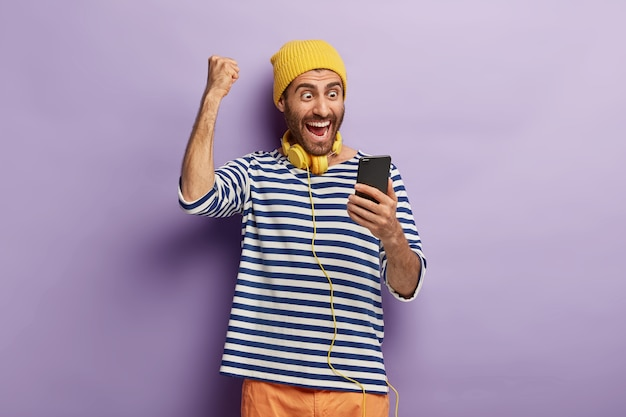 Triumphing happy guy raises clenched fist, celebrates winning lottery, gets message of confirming holds mobile phone, browses social media, wears yellow hat, striped jumper, always stays in touch Free Photo