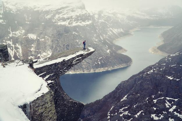 ノルウェーの雪の中でtrolltunga崖。風光明媚な風景です。男旅行者が岩の端に立っていると見下ろしています。旅行、極端で活発なライフスタイル。 Premium写真