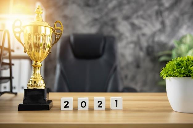 オフィスでの作業用木製テーブル、成功と勝利のコンセプトに関するかわいい年番号2021の優勝者のトロフィー賞 Premium写真
