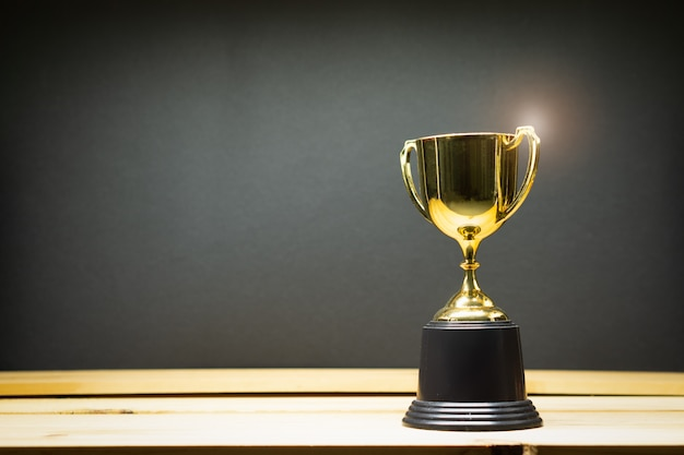Trophy on top of old wooden table in front of blackboard. Premium Photo