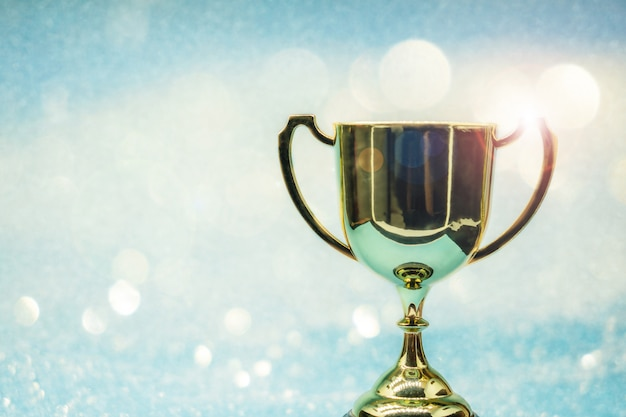 Trophy over wooden table and background bokeh. Premium Photo