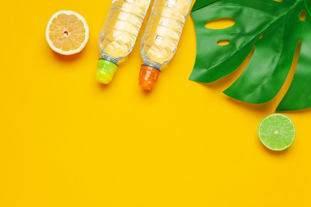 Tropic leaves and bottle water on yellow background. detox fruit infused water. Premium Photo