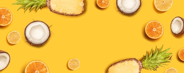 Tropical abstract background. pineapple, lemons, oranges and coconuts on a yellow background. Premium Photo
