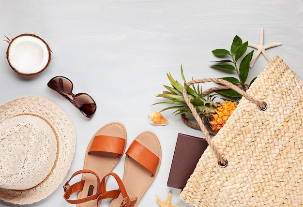 Tropical beach accessories top view with straw summer bag and flip flops Premium Photo