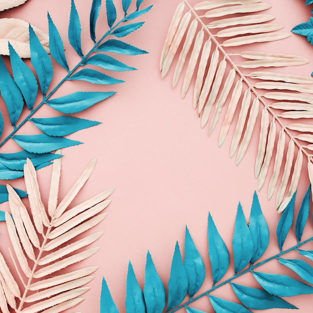 Tropical blue and pink palm leaves on pink background Free Photo