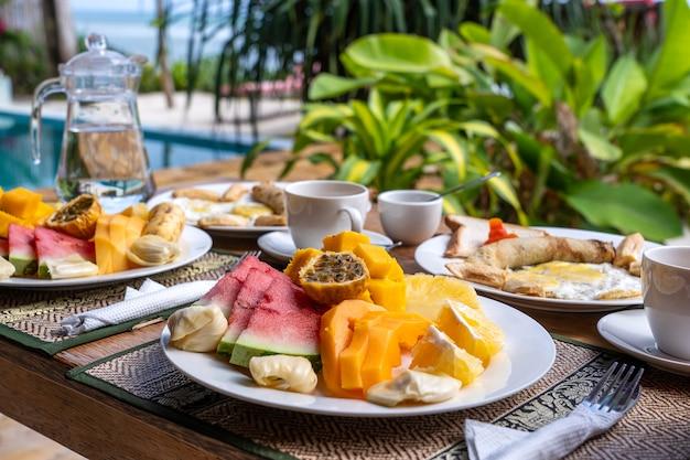 海の近くのビーチでのフルーツ、コーヒー、スクランブルエッグ、バナナのパンケーキのトロピカルブレックファースト Premium写真