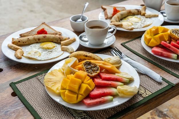 フルーツ、コーヒー、スクランブルエッグ、バナナのパンケーキのトロピカルブレックファースト Premium写真