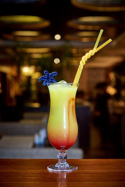 Tropical cocktail on the bar counter on a dark blurred background. Premium Photo