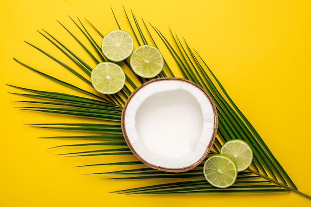 Tropical coconut, palm and lime on a yellow Premium Photo