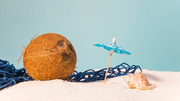 Tropical concept with coconut and beach umbrella Free Photo