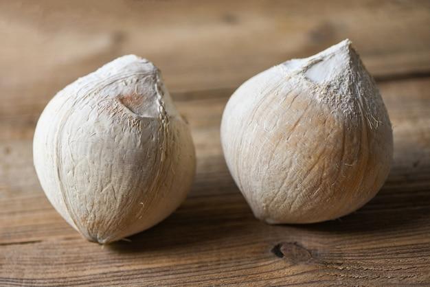 Кокос тропических фруктов на деревянном столе, свежий кокос для еды Premium Фотографии