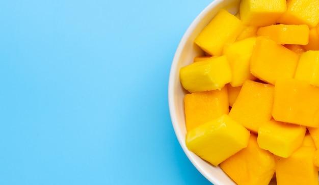 Тропический плодоовощ, куски куба манго в белом шаре на голубой предпосылке. Premium Фотографии