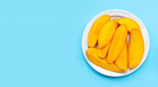 Тропический плодоовощ, куски манго на белом блюде на голубой предпосылке. Premium Фотографии
