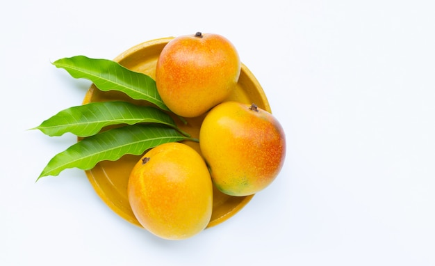 Tropical fruit, mango on yellow plate on white surface. top view