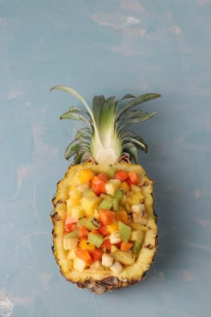 パイナップルの半分のトロピカルフルーツサラダ、水色の背景、クローズアップ、上面図、垂直方向 Premium写真