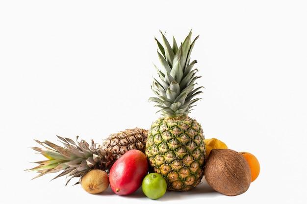 Ассортимент тропических фруктов, изолированные на белом фоне. ананасы, кокос, манго, апельсин, лайм, лимон и киви Premium Фотографии
