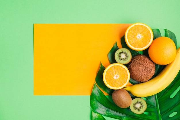 tropical fruits background with card template and palm tree leaf