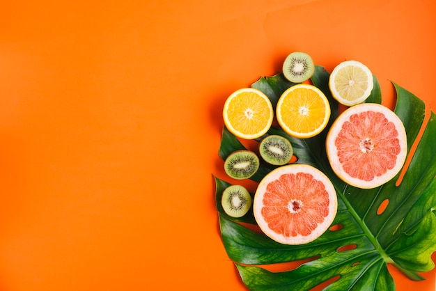 Tropical fruits background with copyspace and palm leaf Free Photo