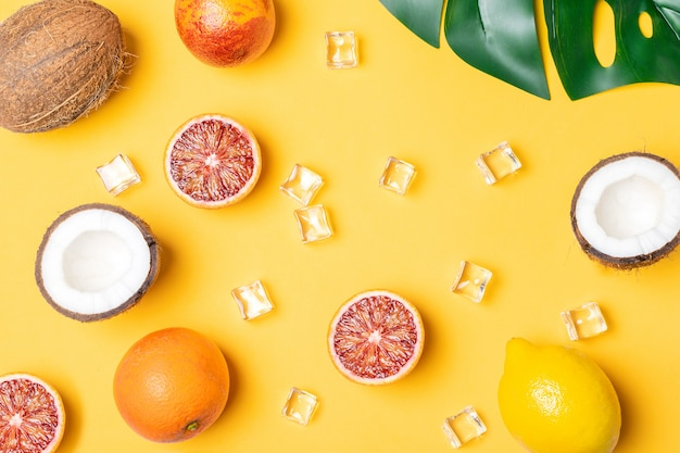 Tropical fruits, blood oranges, coconut, palm leaf Premium Photo