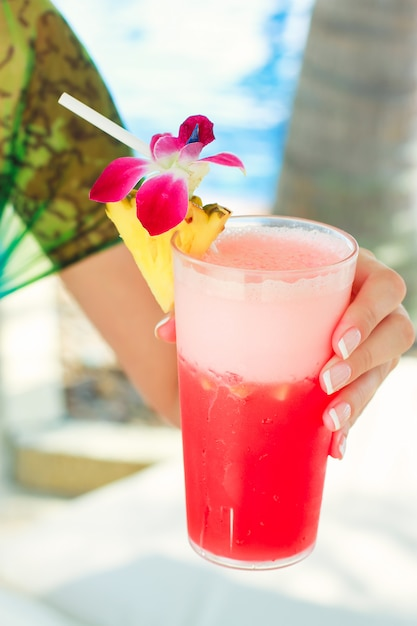 Tropical red cocktail in hand of a young woman on an exotic resort Premium Photo