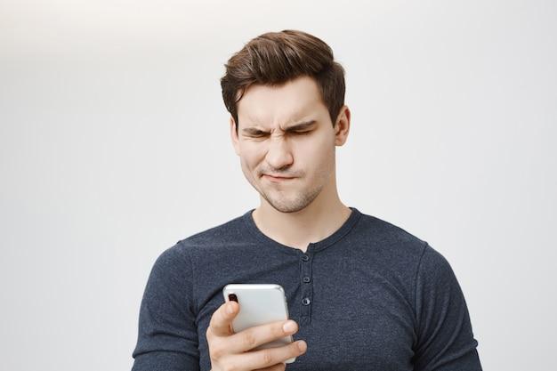 Обеспокоенный сбитый с толку парень, глядя на сообщение мобильного телефона Бесплатные Фотографии