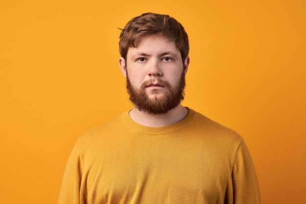고생하는 불쾌한 수염 난 남자는 얼굴을 찌푸리고, 슬프고, 괴로워하고, 화가 났고, 격리에 앉아 지루해하고, 좋은 기회를 놓쳐서 불행하고, 캐주얼 한 옷을 입고, 노란색 배경 위에 격리되어 있습니다. 프리미엄 사진