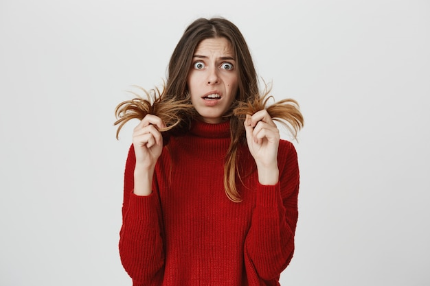 Troubled girl showing split ends Free Photo