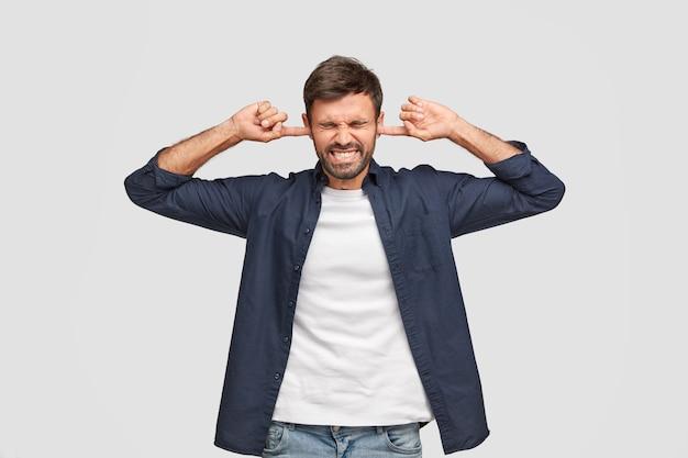 Un uomo di mezza età turbato tappa le orecchie con un'espressione dispiaciuta, stringe i denti Foto Gratuite
