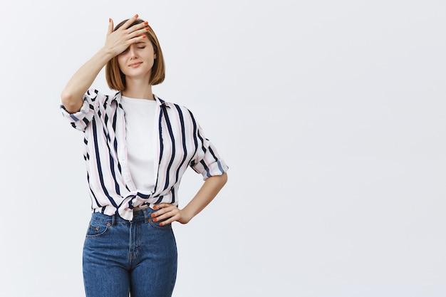 Giovane donna triste turbata che sembra frustrata, tenendo la mano sulla testa e sospirando delusa Foto Gratuite