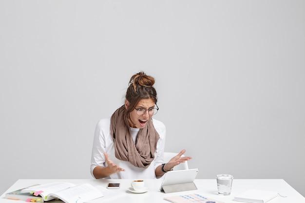 La giovane femmina fastidiosa e preoccupata ha problemi durante il lavoro, non sa come usare il programma sul tablet Foto Gratuite