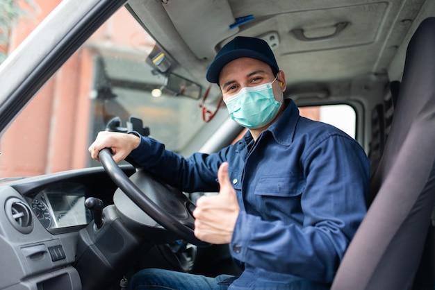 Truck driver giving thumbs up during coronavirus pandemic Premium Photo