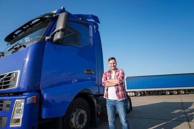 Водитель грузовика в повседневной одежде стоит у своего грузовика со скрещенными руками на стоянке Бесплатные Фотографии