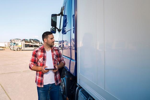 タブレットで彼のトラックのそばに立って、トラックを見ているカジュアルな服を着たトラック運転手 無料写真
