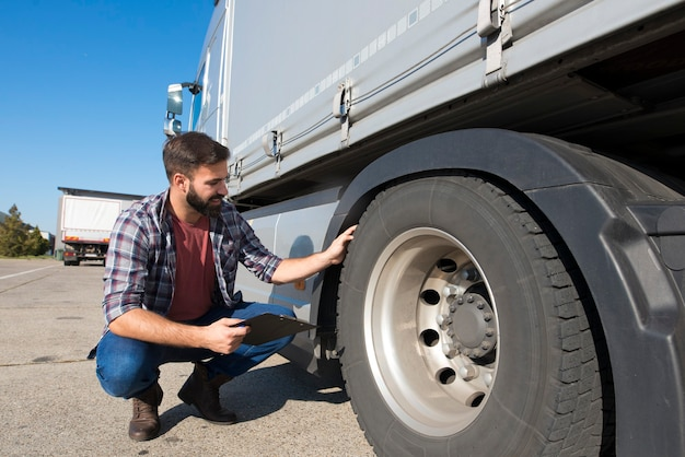 Водитель грузовика осматривает шины и проверяет глубину протектора шины для безопасной езды Бесплатные Фотографии