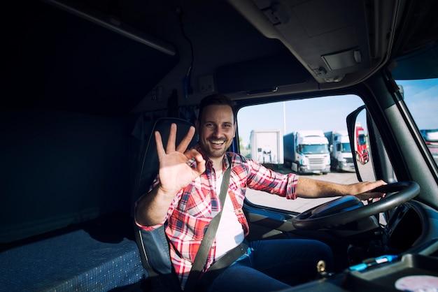 Водитель грузовика любит свою работу и показывает знак жестом `` ок '', сидя в кабине грузовика Бесплатные Фотографии