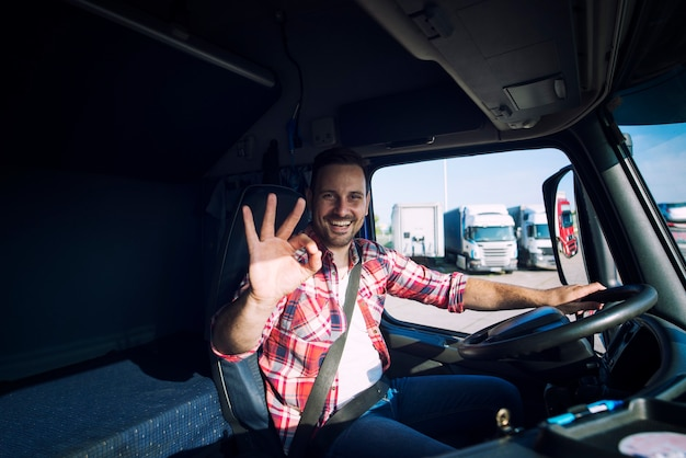 Truck driver loving his job and showing okay gesture sign while sitting in his truck cabin Free Photo