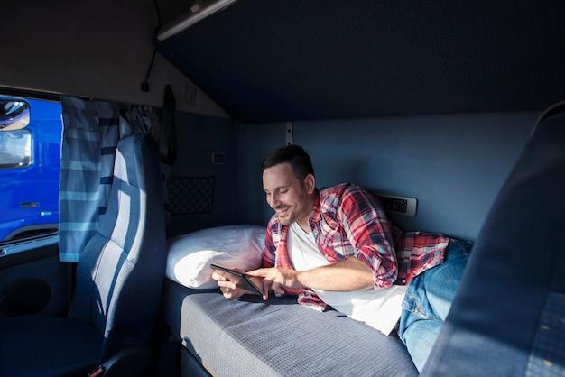 タブレットコンピューターを介して彼の家族と通信する彼のキャビンのベッドに横たわっているトラック運転手 無料写真
