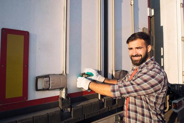 Autista del camion che apre la parte posteriore del rimorchio del camion pronto per scaricare le merci Foto Gratuite