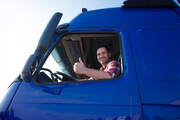 Водитель грузовика показывает палец вверх через окно кабины Бесплатные Фотографии