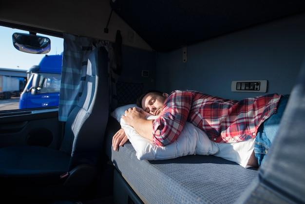 Водитель грузовика спит в своей кабине после сверхурочной работы на длинных маршрутах Бесплатные Фотографии