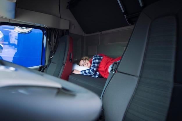 Водитель грузовика спит на кровати внутри салона кабины грузовика Бесплатные Фотографии