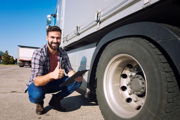 Водитель грузовика с большими пальцами руки проверки состояния шин и проверки давления Бесплатные Фотографии