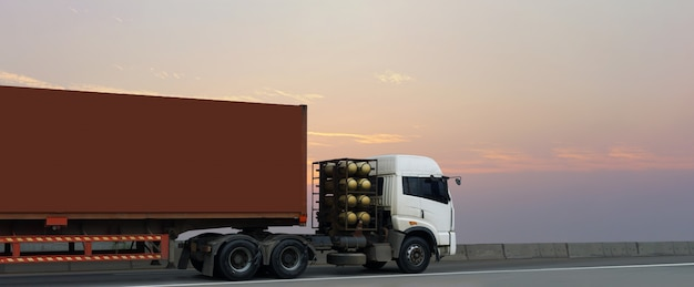 Truck on highway road with red container,logistic industrial with sunrise sky Premium Photo