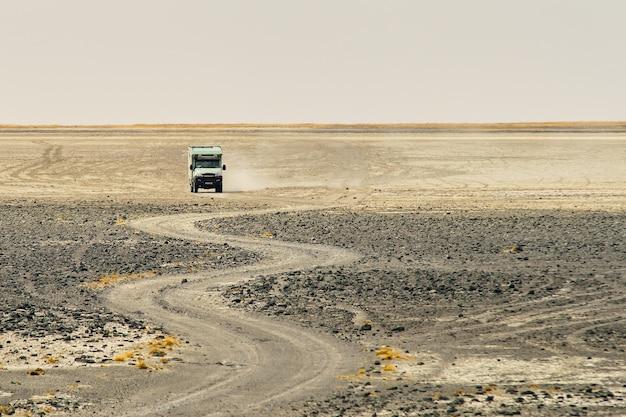ほこりを作る曲がりくねった岩の多い道を通って乗るトラック 無料写真