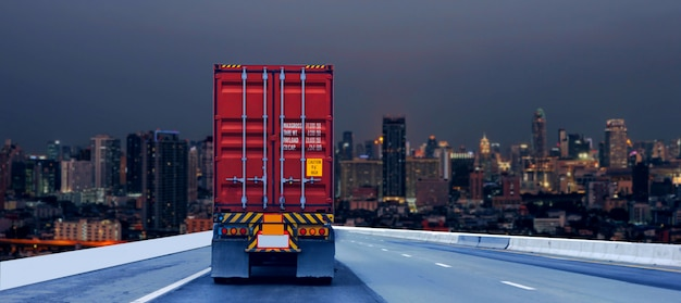 Truck on road with red container, transportation concept.,import,export logistic industrial transporting land transport on the expressway driving to night city Premium Photo